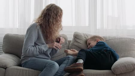 foster : Mom tickles son on the couch
