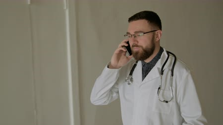 sebész : The doctor is walking with a smartphone in the hospital corridor. Stock mozgókép