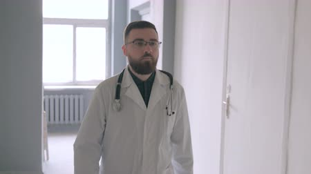 profesyonel meslek : A doctor with a stethoscope goes through the corridor of the hospital. Stok Video