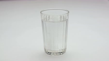 oldódó : Aspirin or effervescent pill dropping into a glass of water.