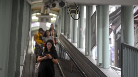 crowded : Hongkong, China - August 2019: Asian people moving on escalator of subway in chinese city on summer day. Front view of adult man and woman get down in metro and using smartphone. Residents and tourists in Hong Kong. Concept: asia, urban, china.