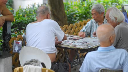 olgun : Hongkong, China - August 2019: asian hong kong senior men playing traditional game with cards and coins at table. elderly friends gambling with money on retirement. asia culture. gamble, communication concept