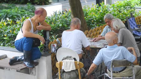 jogadores : Hongkong, China - August 2019: Elderly people playing domino card board game sitting at table in green city park. Mature asian men having time together at desk, compete in traditional popular play on summer day. Concept: chinese, strategy, pastime.