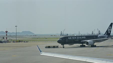nouvelle zélande : Hongkong, China - August 2019: Air new zealand Plane begins to move along runway at airport in asian city on summer. Black airplane moving on airfield in town with beautiful natural landscape of mountain and river. Concept: business, transport, aviation.