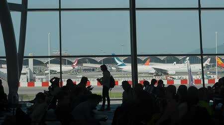 urlop : Hongkong, China - August 2019: People customers waiting for departures and arrival in modern building of international airport. Asian man and woman having time with smartphone in interior and view through window of exterior with airplanes in outside. Conc
