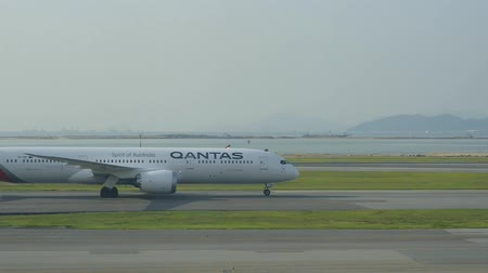 Hongkong, China - August 2019: Plane Qantas Australia moving along runway on background of beautiful nature landscape in city. White airplane running on airfield, landing in asian town with mountains and river on summer day. Concept: travel, aircraft, bus