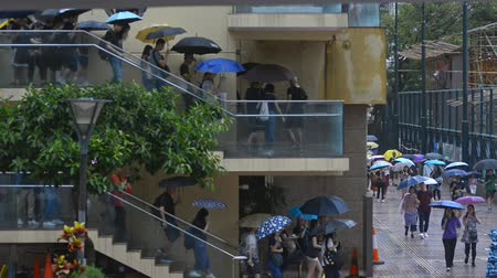 direitos : Hongkong, China - August 2019:hong kong august 2019 protests. Massive crowds of protesters carry umbrellas on building ladder in central Hongkong during rainy weather, peaceful assembly and anti government demonstrations