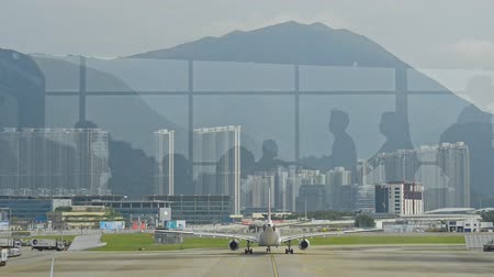 Hongkong, China - August 2019: airplane takeoff view from hong kong international airport. walking people reflection. passengers in waiting room. urban building background. aircraft, runway, departure concept.