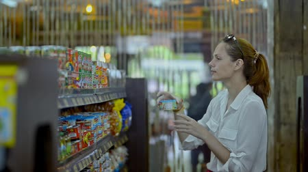 bakkaliye : Bali, Indonesia - March 2019: Young american woman is making food purchase standing in grocery shop. Beautiful brunette choosing and watching olives, putting in basket in supermarket during travel. 30s lady wearing white shirt. Concept: Asia, retail, ever Stok Video