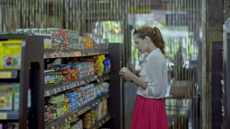 tüketici : Bali, Indonesia - March 2019: Young american woman is choosing food standing near shelves in supermarket. Side of female customer buying canned product, watching and thinking. Redhead lady is on shopping during summer Asia vacation.