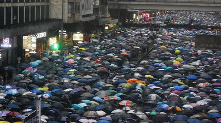 crowded : Hongkong, China - August 2019: Colorful demonstration of people with umbrellas walking along street of asian city. Crowd attends peace rally of five demands in center of Hong Kong on summer day. Top view of town and marching adults in rainy weather. Conce