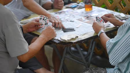 daily : Hongkong, China - August 2019:asian hong kong three senior men playing traditional game with cards and coins at table closeup. elderly friends gambling with money on retirement. asia, communication, domino concept