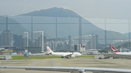 сумки : Hongkong, China - August 2019: plane departure or takeoff on runway through airport window with passengers reflection. aiplane landing on airstrip. in asia, hong kong international aeroport. boarding, gate concept Стоковые видеозаписи