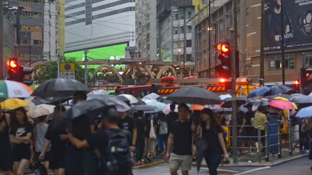 zákaz : Hongkong, China - August 2019: fire truck rides through the crowd. People with umbrellas walking on city street during political meeting. Massive crowds of protesters marching through centre