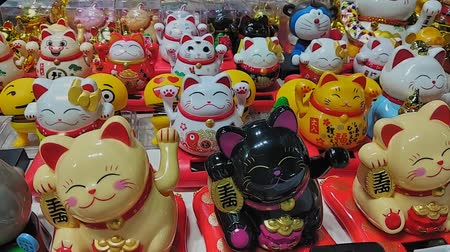 tüketici : Hong Kong, China - August, 2019: souvenir store. Traditional maneki neko lucky cat figurines on display at a market in South East Asia. gift decoration. success symbol. famous doll in row. chinese golden statue