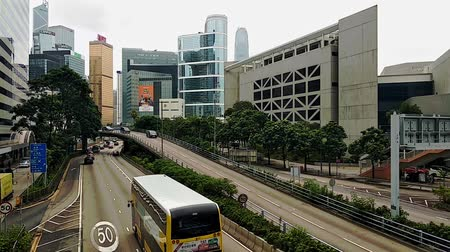 Hong Kong, China - August, 2019: Beautiful view of road traffic and modern buildings in asian city in summer. Cars driving along street with tall houses and green trees in commercial district of metropolis in Asia. Concept: cityscape, transport, architect