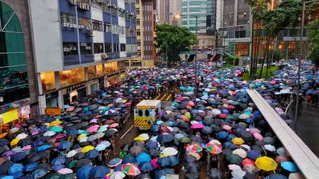 hong kong : Hongkong, China - August 2019: Ambulance drives through the crowd. People with umbrellas walking on city street during political meeting in Hong Kong. protesters attend demonstration