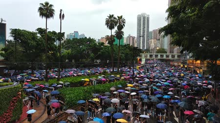 Hong Kong, China - August, 2019: Colorful demonstration in support of five demands on street of asian city. People with umbrellas in hands are walking in town, attend at political march on day of solidarity. Beautiful view of modern metropolis on rainy we