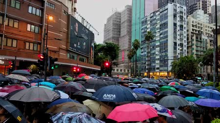 高層 : Hong Kong, China - August, 2019: crowded street, Anti-government protests in Hong Kong. Thousands of pro-democracy protesters walk participate in a mass rally in Hongkong. umbrella and rain