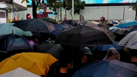 crowded : Hong Kong, China - August, 2019: Adult men and women walking along street during colorful demonstration in Hong Kong. Closeup view of people with umbrellas in hands gathered for peaceful rally in asian city in rainy weather. Concept: meeting, human rights