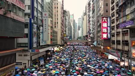 zákaz : Hong Kong, China - August, 2019: view of people crowds of protesters carrying umbrellas against the rain, during anti government demonstrations, politics and activism in China. scyscraper street Dostupné videozáznamy