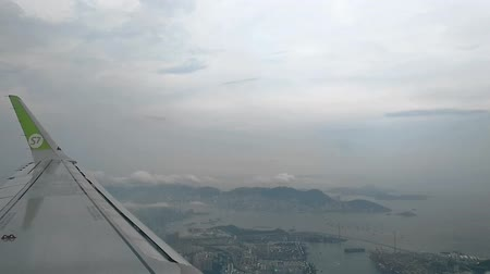 atmosféra : Hong Kong, China - August, 2019: S7 Airplane flight. Wing of an aircraft. View from the window of plane above hong kong. Passenger In flight. engine flying above the land. takeoff or landing, airline concept Dostupné videozáznamy