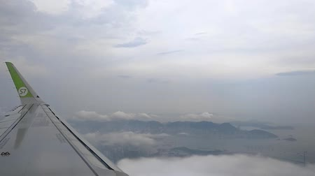 Passenger plane flying over asian metropolis and sea on foggy morning. Beautiful aerial view of wing of airplane flies in blue sky above city and amazing nature with mountains and waters on summer. Concept: travel, aircraft, transport. Vidéos Libres De Droits