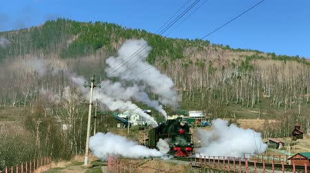 mozdony : Lake Baikal, Russia - August, 2019: Old locomotive moving along railway station in countryside on autumn day. Black train runs on rail platform extruding white steam in area with mountains and houses under blue sky. Concept: tourism, railway, landscape. Stock mozgókép