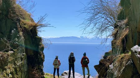 Lake Baikal, Russia - August, 2019: People tourists looking at sea and mountains standing on shore on sunny day. Back view of three adults enjoying natural scenery of blue cliffs and waters during baikal traveling. Concept: vacation, tourism, lifestyle. Vidéos Libres De Droits