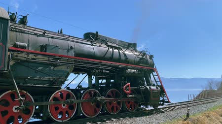 puffing : Lake Baikal, Russia - August, 2019: Old locomotive with steam is standing on rail road in beautiful natural countryside. Train is in area with blue mountains and waters on sunny day. Rail transport and beauty of unique nature. Concept: tourism, scenic, en
