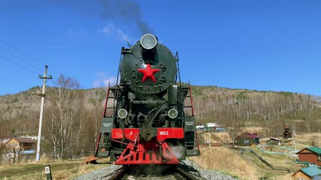 woodland : Lake Baikal, Russia - August, 2019: Beautiful view of old locomotive and nature in countryside on fall day. Front of train emits smoke while standing on railway in area with mountains and houses under blue sky. Concept: transport, tourism, landscape.