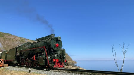 mozdony : Lake Baikal, Russia - August, 2019: Old steam train standing on railway in beautiful countryside on autumn day. Black rail machine with red star emits smoke while standing on platform by blue lake with unique nature. Vintage locomotive and amazing landsca Stock mozgókép