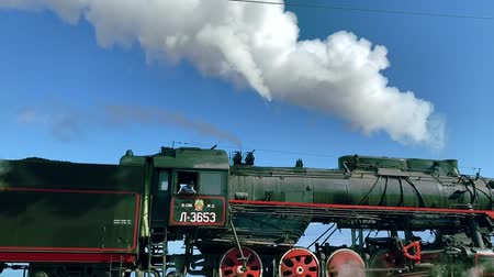 mozdony : Lake Baikal, Russia - August, 2019: Old locomotive with steam moving along railroad in picturesque countryside on sunny day. Train with freight moves in natural area with blue mountains, sky and sea in summer. Concept: railways, transportation, landscape. Stock mozgókép