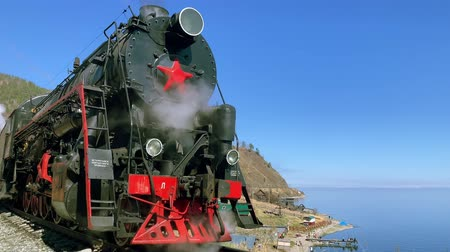 water rail : Lake Baikal, Russia - August, 2019: Old russian locomotive stands on railway by Baikal lake on autumn day. Vintage black transport puffs with steam standing on rail platform in area with mountains and blue waters in sunny weather. Concept: traveling, natu
