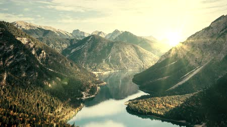 A slow motion camera zoom in a mountainous scenery with a river running along and the sun behind the mountains. Wideo