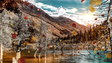 A slow motion camera zoom in a mountainous landscape with snowy peaks and autumn leaves falling down.