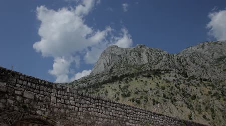leisure time : Old masonry Montenegro Timelapse, fortification, a slow increase in size and panorama clouds flying across the sky and on the ground running shadows of clouds.