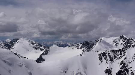deep snow : Stock Video Footage Aerial View Deep dip snow crater  Snow lies in the folds and crevices, it is an eternal snow, we were flying over the mountains, as high as you do not take off any living creature here just rocks, snow and ringing air. Stock Footage