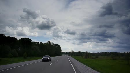 řídit : Stock Video Footage turn Speed drive and a sharp turn, cloudy sky, a wall of green trees on both sides of the road