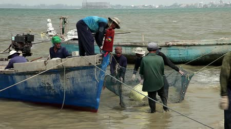 fishing industry : Stock video footage Fishermen return from the sea with their catch, they pulled heavy nets ashore and sorting the catch, to put in the basket. Fishing boats rock in the surf at the beach. Summer, Tropical, Asia, Lifestyle