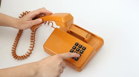 устаревший : Woman is pressing the buttons of old orange telephone