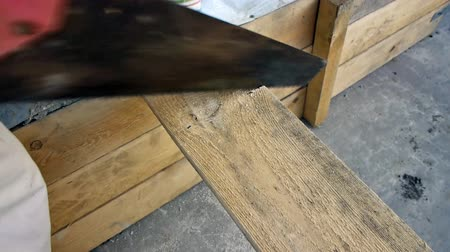 velo : Sawing the plank with a hand saw, closeup view