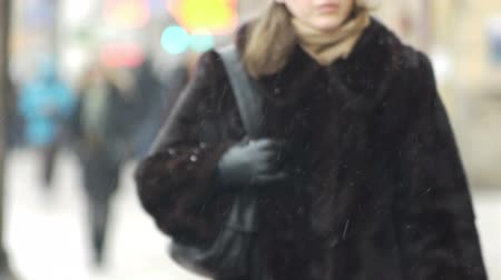 kasaba : Pedestrians in winter casual clothes walking on pavement in snowy day, blurred and unfocused