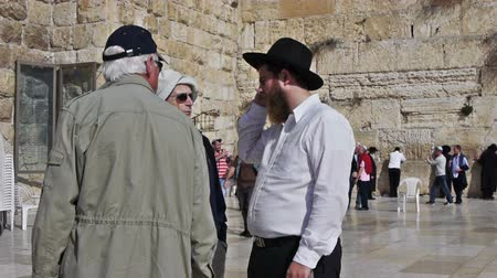 jerozolima : JERUSALEM, ISRAEL - NOVEMBER 11, 2011: True believer talking with tourists near Western Wall (Wailing Wall or Kotel).