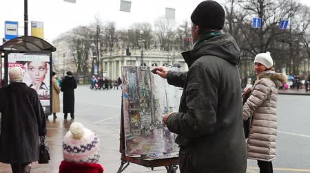 oilpaint : SAINT PETERSBURG, RUSSIA - JANUARY 05, 2014: Elder artist painting from nature at street near bus stop in winter day.