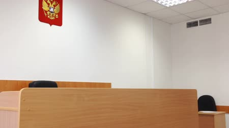 стулья : Interior of empty court room with Russian National Emblem at the wall Стоковые видеозаписи