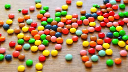 colorful candy : Colorful candies bouncing off the wooden table surface