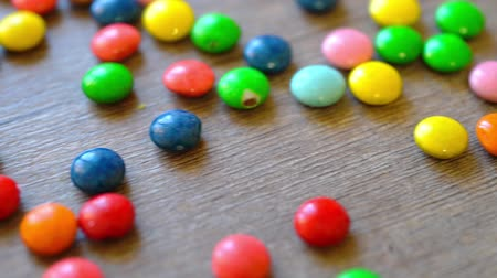 raf : Colorful candies bouncing off the wooden table surface