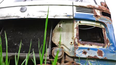 poškozené : Close up view at old rusty car in scrapyard through the grass