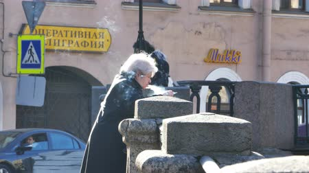SAN PIETROBURGO RUSSIA 18 mar 2015: Old Lady Smoking at River Embankment con Lotto di fumo attorno a lei